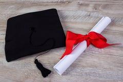 tampão da graduação, chapéu com papel do grau no conceito de madeira da graduação da tabela fotos de stock royalty free