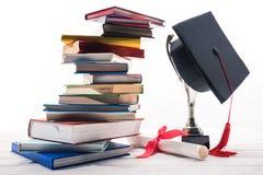 Tampão da graduação no copo do troféu por livros e por diploma foto de stock royalty free