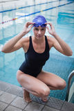 Tampão da mulher bonita óculos de proteção de agachamento e vestindo da nadada e Foto de Stock Royalty Free