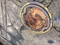 Tampão de gás amarelo oxidado no passeio à terra concreto com quebras foto de stock royalty free