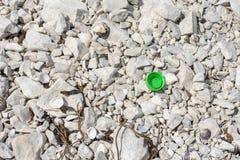 Tampão de garrafa verde que coloca em rochas fotografia de stock royalty free