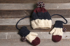 Tampão do inverno e mitenes feitos malha no fundo de madeira Fotografia de Stock