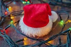 Tampão e festão de Santa Claus no fundo de madeira fotografia de stock
