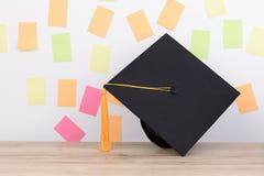 Tampão graduado preto e borla amarela na tabela de madeira, p colorido imagem de stock