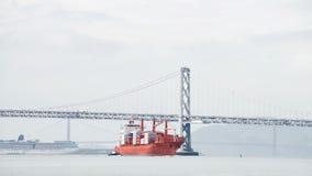 TAMPÃO PORTLAND do navio de carga que viaja sob a ponte da baía fotografia de stock