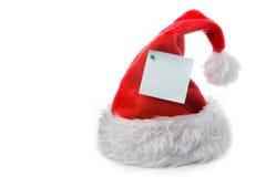 Tampão vermelho de Papai Noel com nota Fotografia de Stock Royalty Free