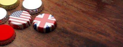 Tampões da cerveja com as bandeiras do Reino Unido e dos EUA no fundo de madeira, espaço da cópia, bandeira ilustração 3D Imagens de Stock