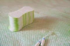 Tampões e almofadas higiênicos em um fundo textured de turquesa Meios do espaço íntimo fêmea do close-up e da cópia da higiene foto de stock