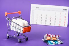 tampões no carrinho de compras, em comprimidos e no calendário pequenos imagens de stock