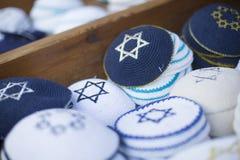 Tampões religiosos judaicos (yarmulke) no pavimento de pedra perto da loja de lembrança no quarto judaico da cidade velha imagens de stock