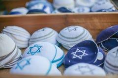 Tampões religiosos judaicos (yarmulke) no pavimento de pedra perto da loja de lembrança no quarto judaico da cidade velha fotos de stock
