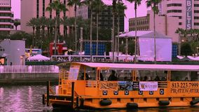 Water taxi sailing on Hillsborough river on sunset sky background in downtown area.