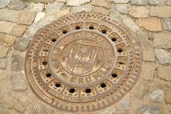 Tampa de câmara de visita do ferro fundido com o emblema da cidade foto de stock royalty free