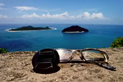 Tampa de lente, vidros, ilhas, e oceano imagem de stock