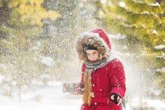 Tampa de neve uma menina no revestimento vermelho no parque no inverno Fotografia de Stock Royalty Free