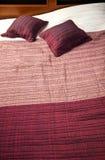 Tampa e coxins roxos de cama Foto de Stock