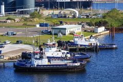 Three Blue and White Tugboats at Industrial Pier stock image