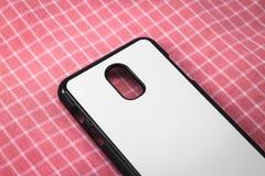 Tampa móvel preta no fundo cor-de-rosa da toalha de mesa Ideia traseira da caixa do telefone e da superfície branca para seu proj fotos de stock