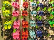 Tampa USA - Maj 10, 2018: Rack med massor av par av barns mjuka rubber sandaler eller Crocs i olika rosa färger, blått Royaltyfri Foto