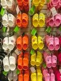 Tampa USA - Maj 10, 2018: Rack med massor av par av barns mjuka rubber sandaler eller Crocs i olika rosa färger, blått Royaltyfri Bild