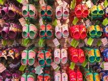 Tampa USA - Maj 10, 2018: Rack med massor av par av barns mjuka rubber sandaler eller Crocs i olika rosa färger, blått Royaltyfri Fotografi