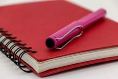 Tampa vermelha do caderno e pena cor-de-rosa Fotos de Stock Royalty Free