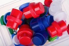 Tampas plásticas coloridas em uma caixa no fundo branco Fotos de Stock