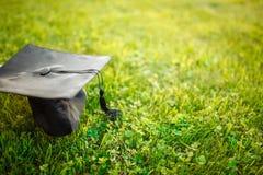 Tampe o graduado, encontrando-se no gramado, grama verde, possa ser usado para o anúncio fotos de stock royalty free