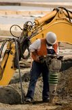 Tamper. A construction worker using a large soil tamping machine stock photo