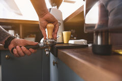 Tamper with portafilter in use by the coffee maker Stock Image