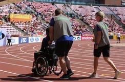 TAMPERE, FINLANDIA, Lipiec 10: Medyczni asystenci pomaga zdradzonej atlety w IAAF Światowym U20 mistrzostwie w Tampere, Finlandia obraz stock