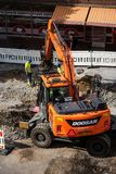 Tampere tramline construction- Doosan excavator digging. And worker supervising- Tampere, Finland in July 2017 royalty free stock photos