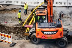Tampere tramline construction- Doosan excavator digging. And workers supervising and fixing pipes- Tampere, Finland in July 2017 stock photography
