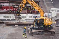 Tampere tramline construction- Doosan excavator digging. Tampere tramline construction- Hyundai excavator digging and worker supervising- Tampere, Finland in Stock Photo