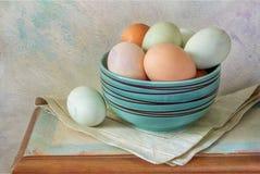 Tampo da mesa com ovos da páscoa e a bacia azul imagens de stock