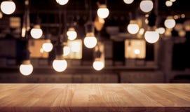 Tampo da mesa de madeira borrado sobre da loja contrária do café com fundo da ampola foto de stock royalty free