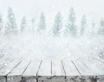 Tampo da mesa de madeira branco na queda de neve borrada na estação do inverno imagem de stock