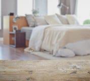 Tampo da mesa de madeira com borrão do interior moderno do quarto com os descansos brancos na cama fotos de stock royalty free