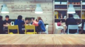 Tampo da mesa de madeira com borrão dos povos no fundo da loja do café da comunidade imagens de stock royalty free