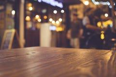 Tampo da mesa de madeira com borrão da iluminação na comunidade do restaurante do café da noite foto de stock