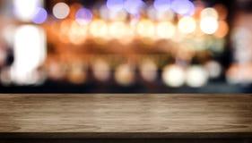 Tampo da mesa de madeira com contador da barra do clube noturno do borrão com luz do bokeh foto de stock royalty free