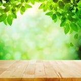 Tampo da mesa de madeira com folha & fundo verdes do bokeh do borrão fotos de stock