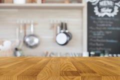 Tampo da mesa de madeira com fundo da cozinha do borrão fotografia de stock