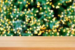 Tampo da mesa de madeira com fundo do bokeh da luz decorativa na árvore de Natal Foto de Stock