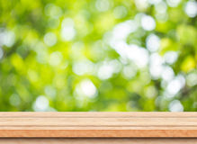 Tampo da mesa de madeira marrom vazio com fundo do bokeh da árvore do verde do borrão Fotografia de Stock Royalty Free