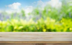 Tampo da mesa de madeira na árvore do borrão, jardim no fundo da manhã Conceito do verão foto de stock
