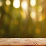 Tampo da mesa de madeira na obscuridade do borrão - fundo verde com efeito do bokeh Fotos de Stock Royalty Free