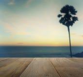 Tampo da mesa de madeira na opinião borrada do por do sol com palmeira da silhueta imagens de stock royalty free