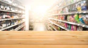Tampo da mesa de madeira no borrão do fundo da prateleira do produto do supermercado fotografia de stock