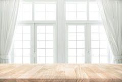 Tampo da mesa de madeira no borrão da janela branca com fundo da cortina imagens de stock